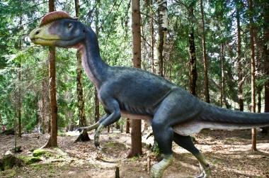 Dinozaur z boku na tle drzew